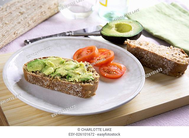 Fresh avocado on thick sliced whole wheat bread with tomatoes