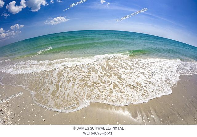 Small wave in the Gulf of Mexico on Gasparilla Island Florida washing up onto the beach taken with a fisheye lens