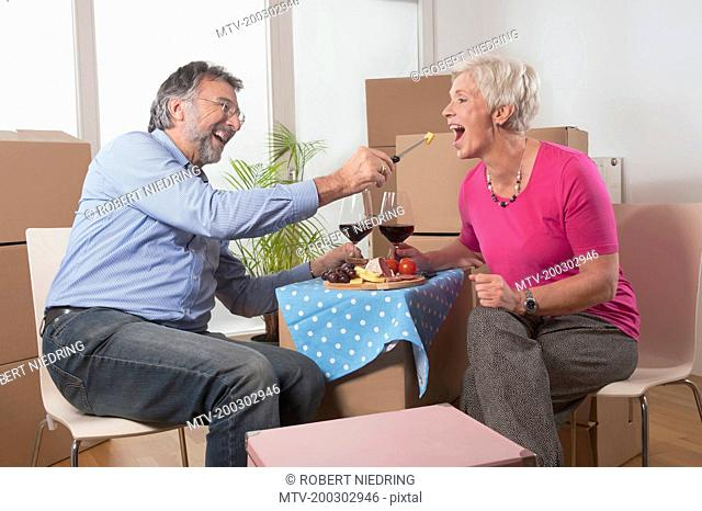 Senior man feeding food to his wife in new home, Bavaria, Germany