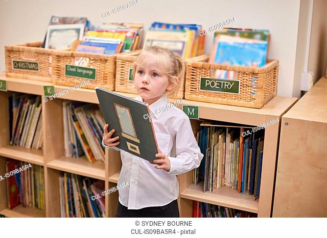 Cute schoolgirl holding book in classroom at primary school