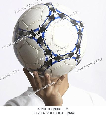 Close-up of a boy covering his face with a soccer ball