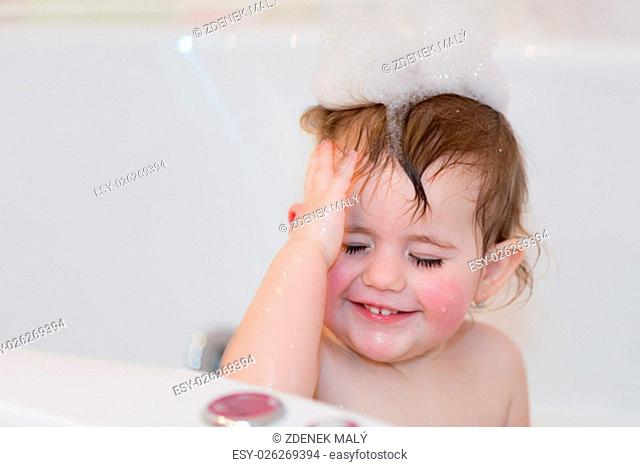 Happy cute little girl taking spa bath at home in water with foam and bubbles