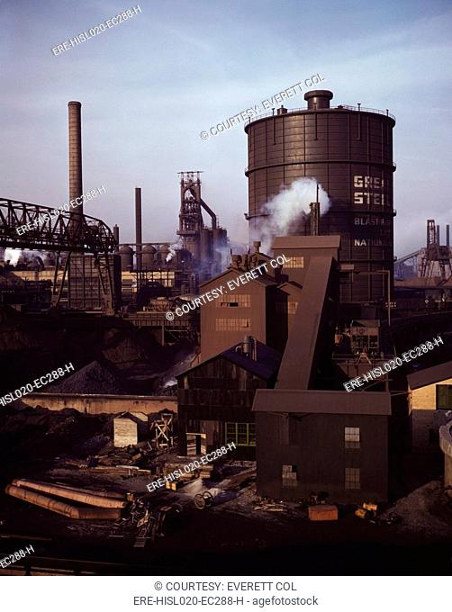 Hanna furnaces of the Great Lakes Steel Corporation, Detroit, Michigan. The tank stores gas from the coke oven. Square building and extension in middle ground...