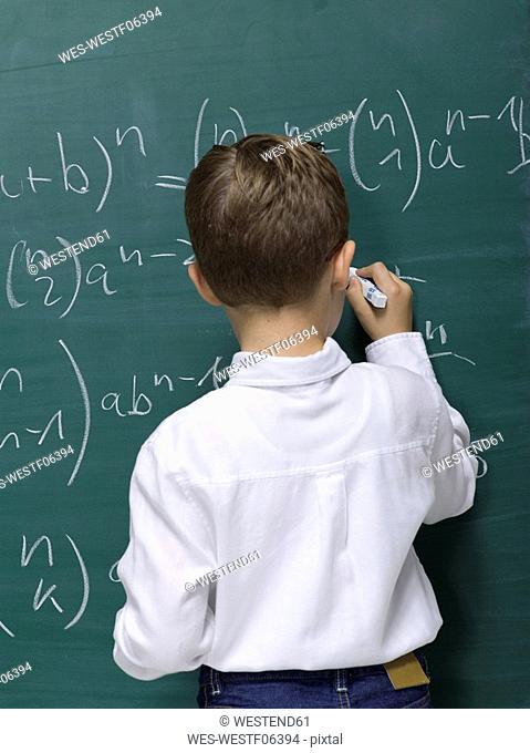 Boy 10-11 writing on blackboard, rear view
