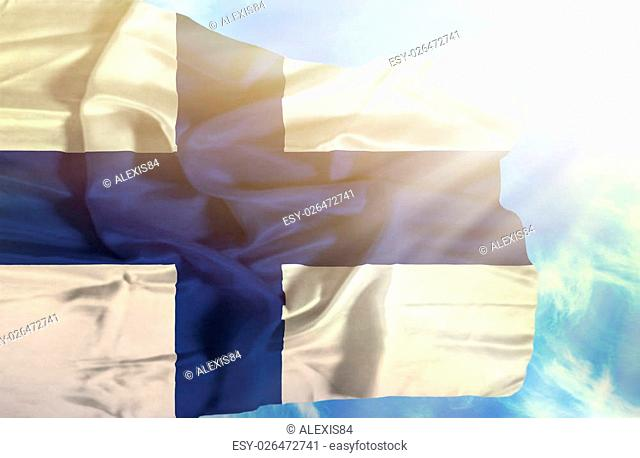Finland waving flag against blue sky with sunrays