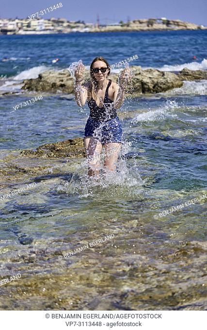woman splashing water in sea. Crete, Greece