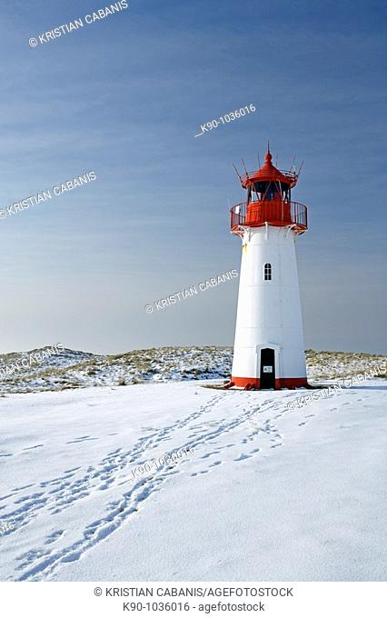 Lighthouse List West on snow covered dunes showing tracks of people leading to the lighthouse, with a bright blue sky at a sunny day, Sylt, Northfrisian Islands