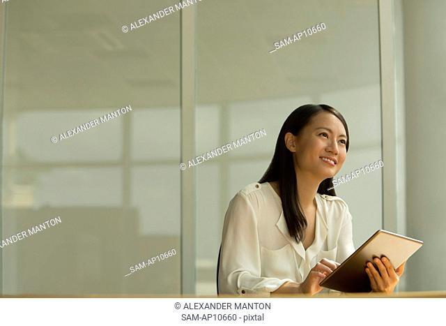 Singapore, Mid adult woman using digital tablet