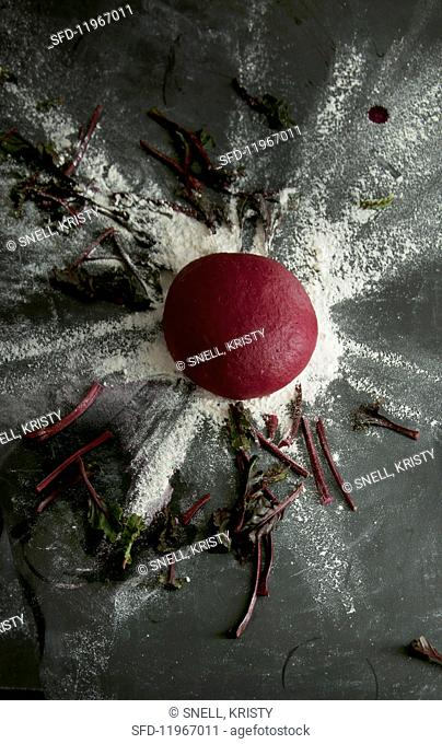 A ball of beetroot pasta dough on a floured surface