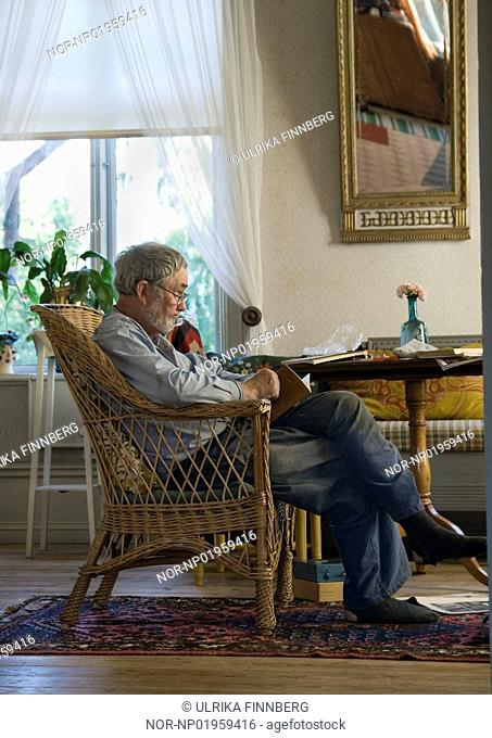 A old man is sitting in a wicker chair, reading a book