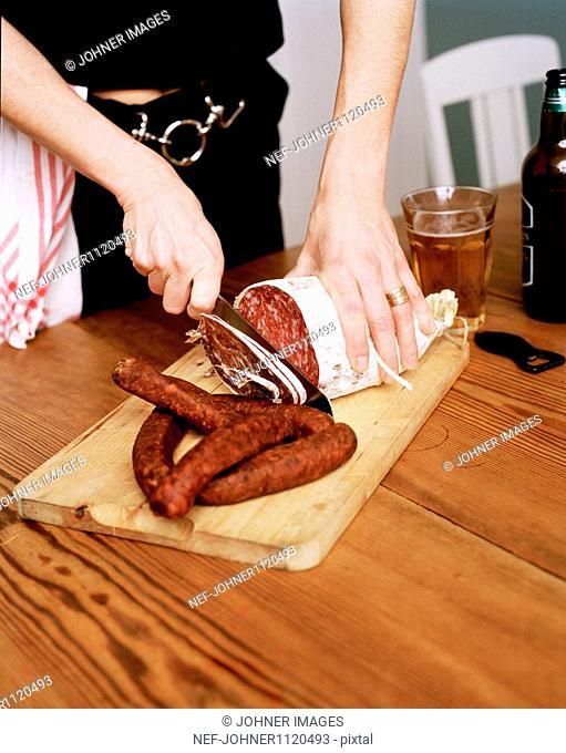 Woman cutting sausage on chopping board
