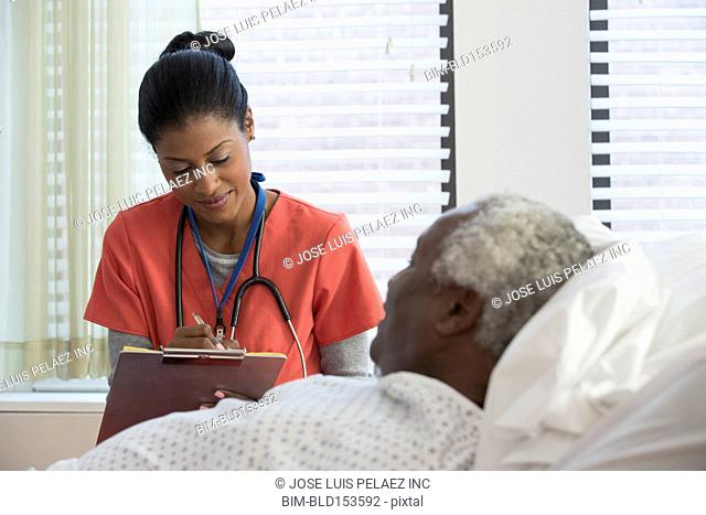 Nurse taking notes with older man in hospital bed