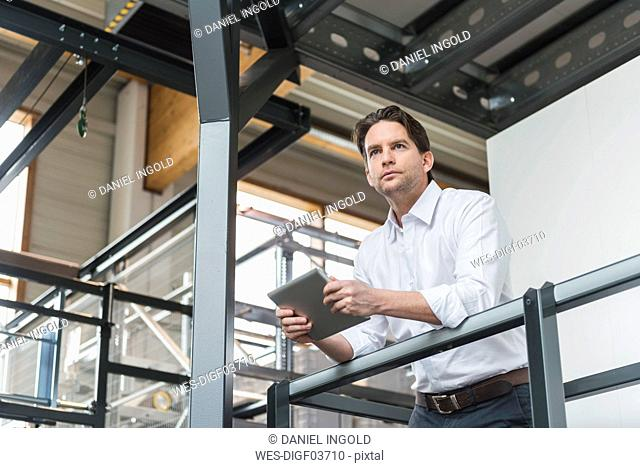 Businessman with tablet in factory thinking