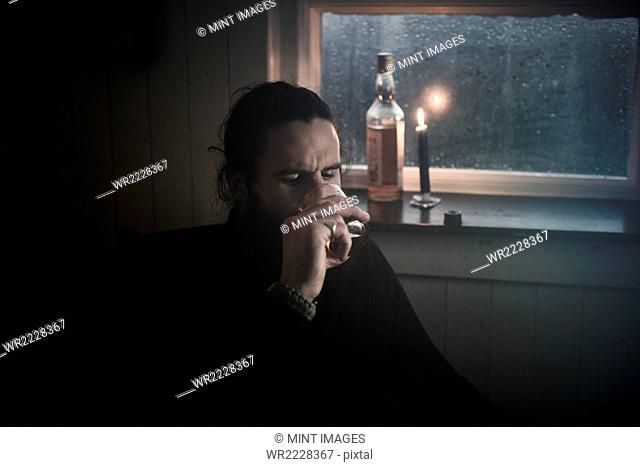 A man sitting in the dark by a window in candlelight drinking from a small glass. A bottle beside him