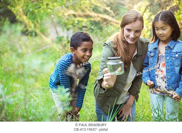 Student and teacher examining insect in jar
