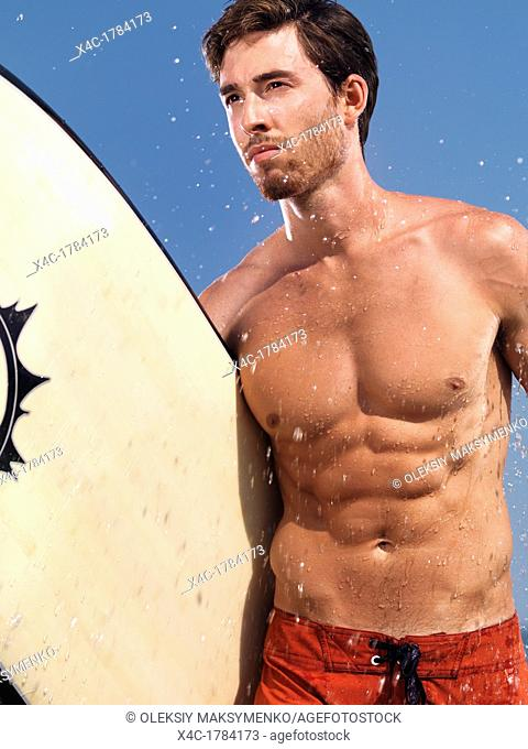 Expressive portrait of a young muscular man with a surfboard at the sea enjoying summer sport activities