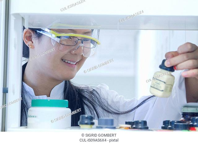 Female scientist selecting chemical from shelf in laboratory
