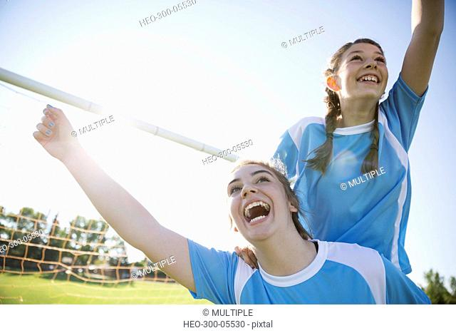 Exuberant middle school girl soccer teammates celebrating and cheering on sunny field