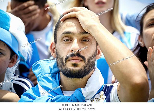Argentinian football fan holding hand on head in disappointment at match