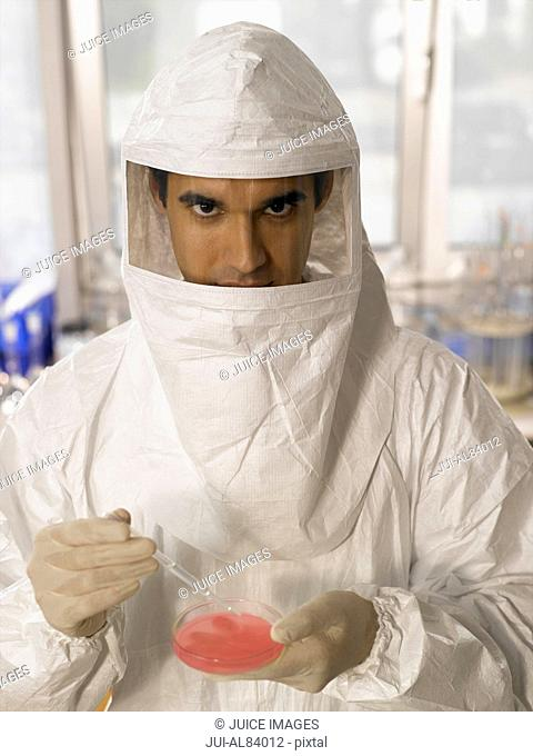 Male scientist in protective suit examining substance in Petri dish