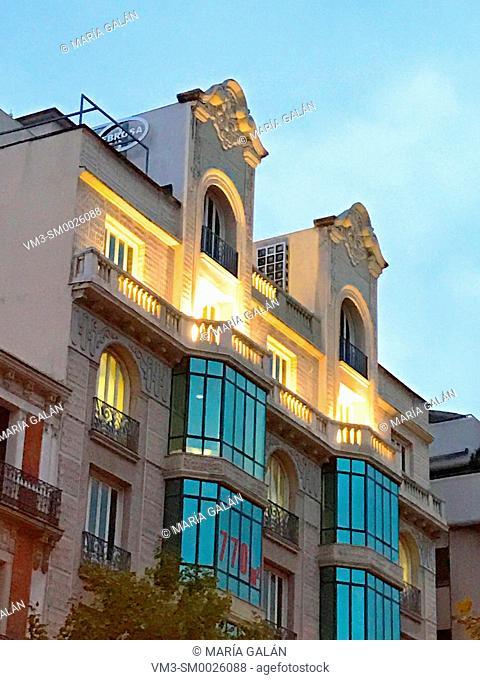 Facade of building, night view. Serrano street, Madrid, Spain