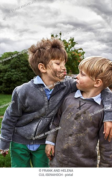 Brothers with muddy faces, arm around