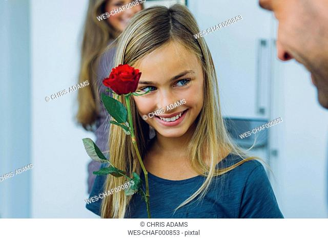 Smiling girl with parents holding rose