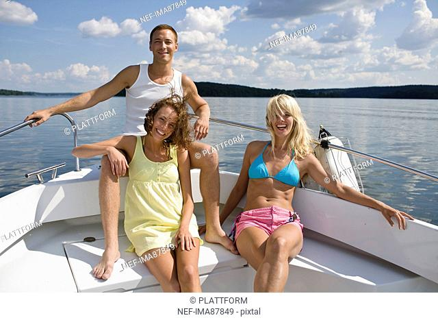 Two young women and young man sitting in yacht on lake