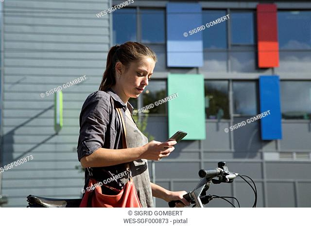Young woman with bicycle reading SMS on her smartphone