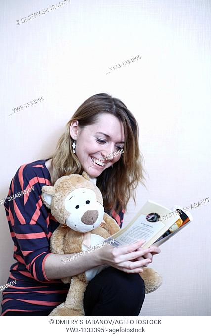 pretty girl against light wall with book and teddy bear
