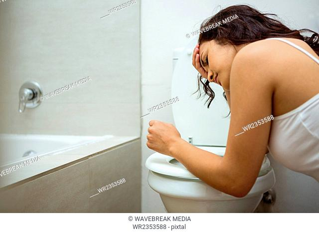 Young woman about to vomit into a commode toilet