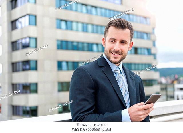 Smiling businessman with cell phone in front of office building