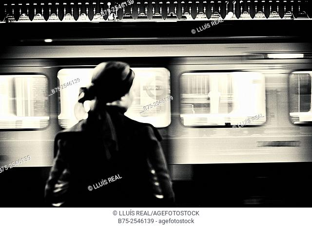 Back view of silhouette of a woman waiting for the train on the underground platform in Upton Park station, with a moving train in the background