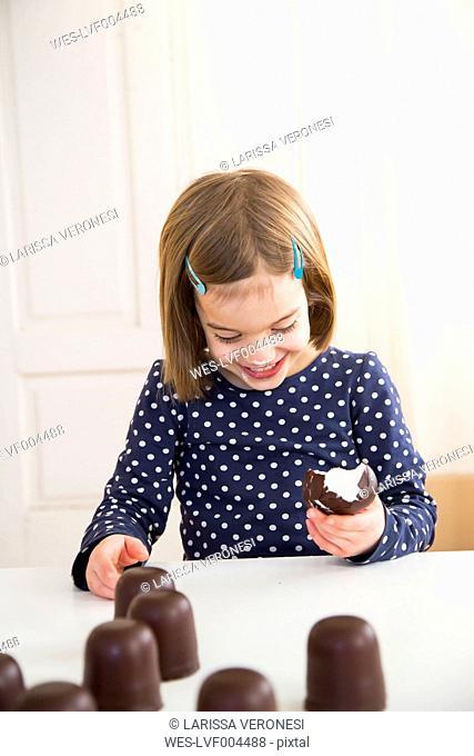 Little girl eating chocolate marshmallow