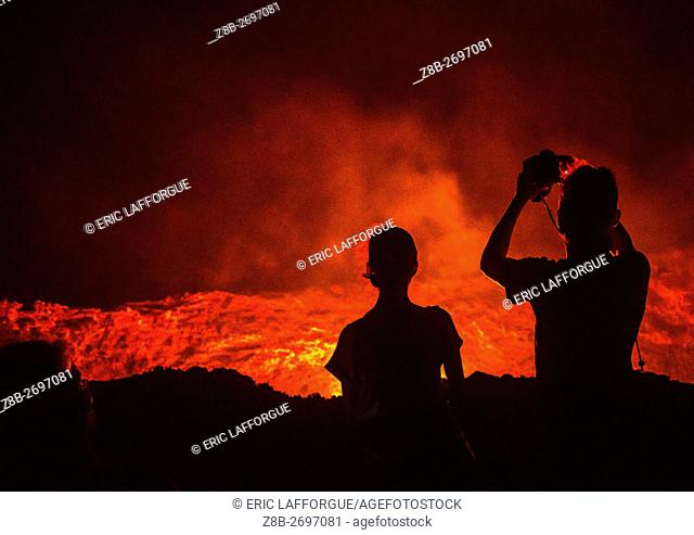 Ethiopia, Afar Region, Erta Ale, tourists taking pictures in front of the living lava lake in the crater of erta ale volcano