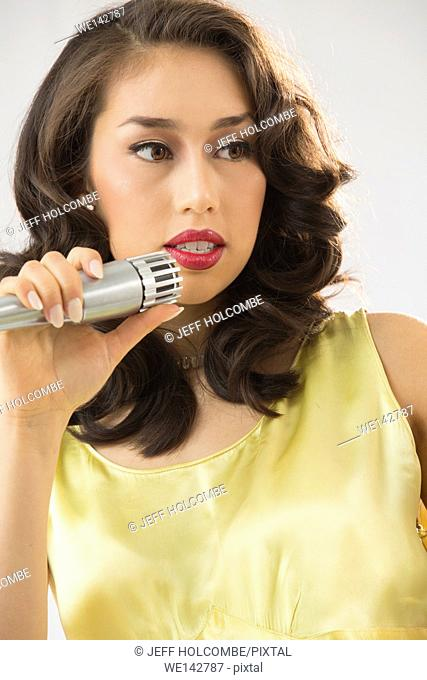 Beautiful young woman head and shoulders, singing or speaking into microphone while looking aside, emphasis in clenched teeth