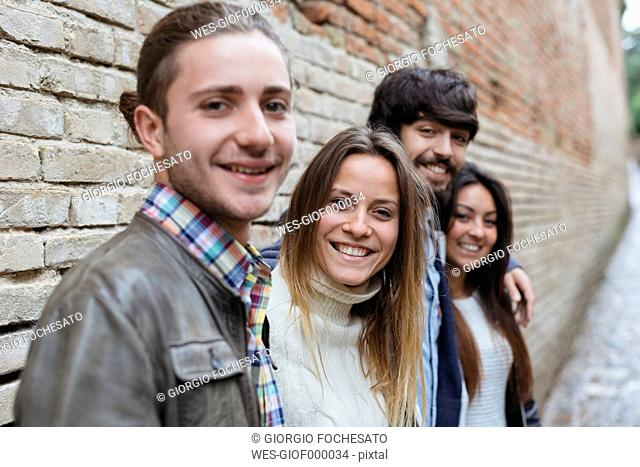 Italy, San Gimignano, group picture of four smiling friends
