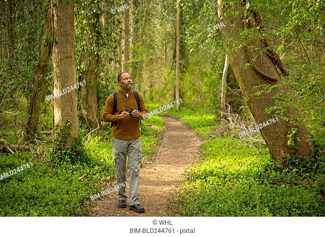 African American man walking on path in forest holding binoculars