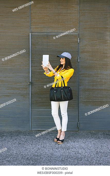 Spain,Catalunya, Barcelona, young modern woman with yellow jacket photographing herself