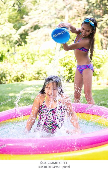 Mixed race girls splashing in wading pool
