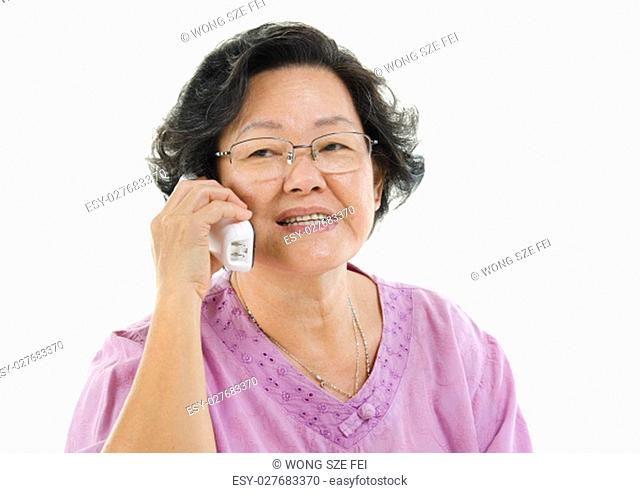 Portrait of Asian senior adult woman calling on phone, isolated on white background