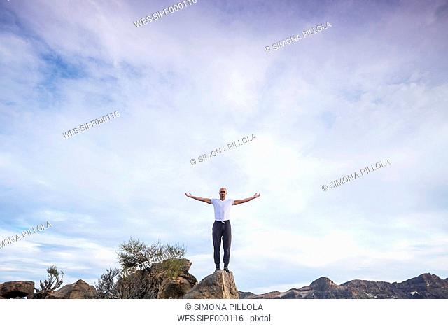 Spain, Tenerife, man with outstretched arms standing on a rock