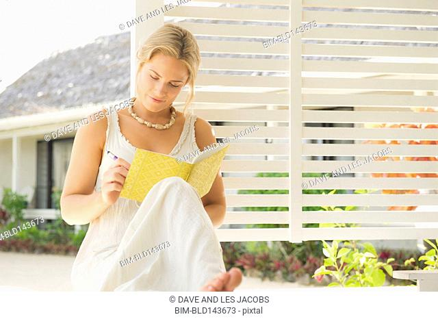 Caucasian woman writing on porch