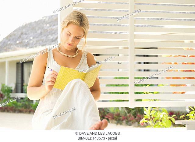 Caucasian woman writing on porch