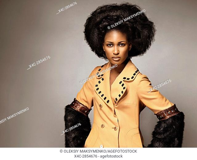 High fashion edgy beauty portrait of a black african american woman wearing an orange coat with black fur on gray background