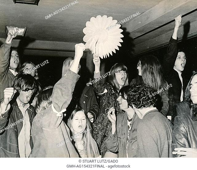 A large group of students wearing hippie attire hold flowers and flower cut-outs aloft during an anti Vietnam War student sit-in protest at North Carolina State...