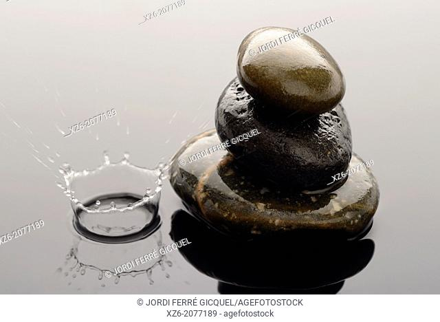 Three Spa stones on water and a close up of a water droplet splashing