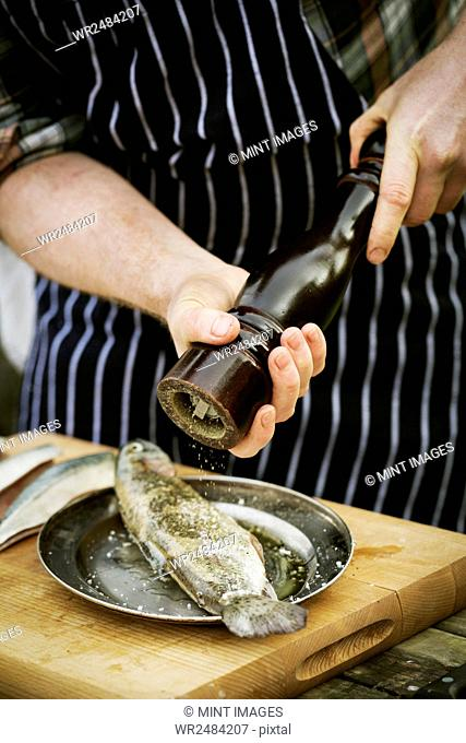 Chef using a salt mill, grinding salt onto a fresh fish