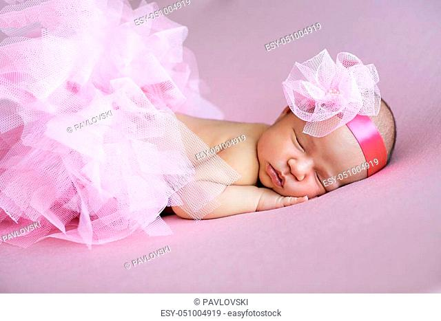 Cute young sleeping baby girl in a pink tutu and headdress