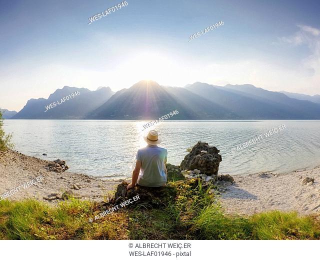 Italy, Lombardy, back view of man sitting at Lake Idro at sunset